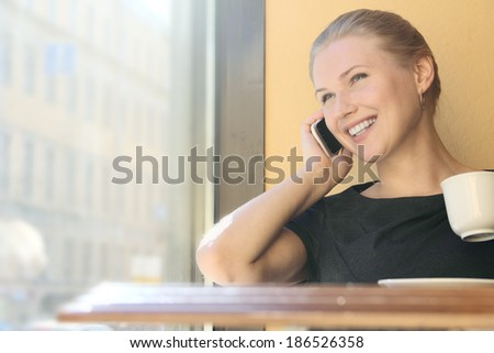 Young attractive business woman talking on the phone in a cafe - stock photo