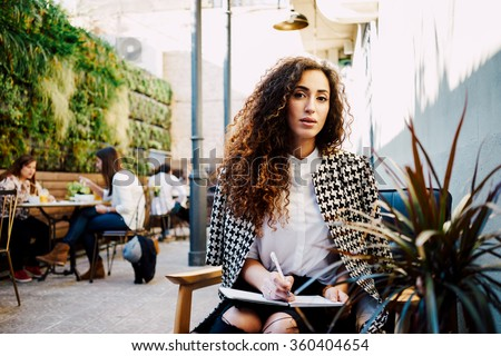 Young attractive business woman with long curly hair holds a job interview in a coffee-shop.beautiful girl takes a journalist interviews - stock photo