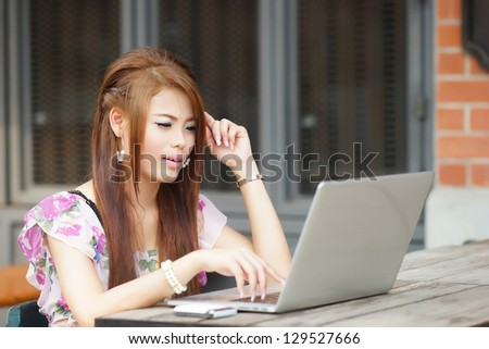 Young attractive business woman working on her laptop at outdoors cafe,  She look very bored and stressed.