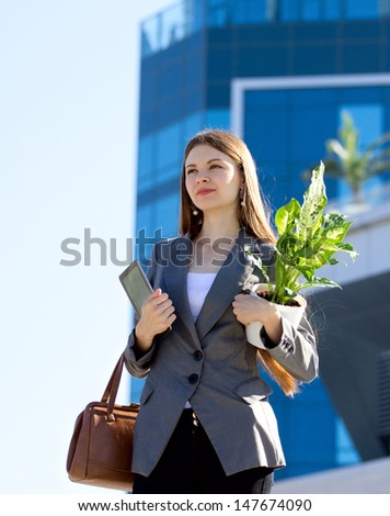 young attractive business women with flower and pad outdoors, looking away,  on building blurred background - stock photo