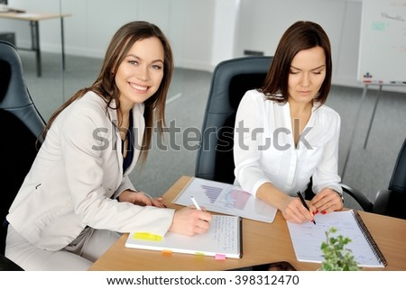 Young attractive business women working in an office. - stock photo