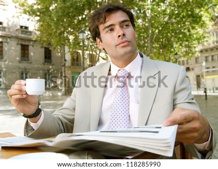 Young attractive businessman being thoughtful while reading the newspaper and sitting at a coffee shop terrace table, outdoors, in a classic city square with trees. - stock photo