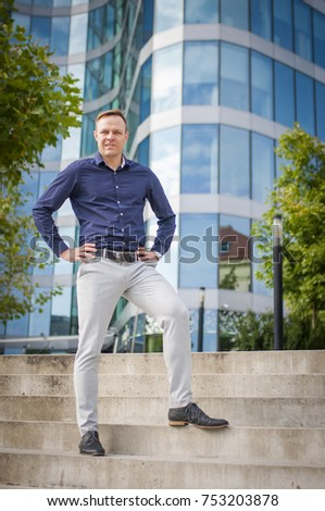 Young attractive businessman dressed casual standing in front of business centre. Fashion man model cool looking.