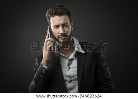 Young attractive businessman having a phone call with his smartphone