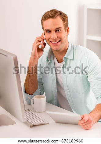 Young attractive businessman in casual clothes using tablet, talking on the phone and smiling while working in office - stock photo