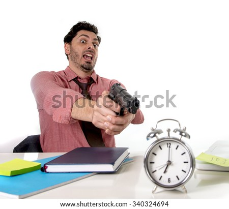 young attractive businessman in stress at office computer desk pointing hand gun to alarm clock in out of time and project deadline expiring concept in angry  and frustrated face expression - stock photo