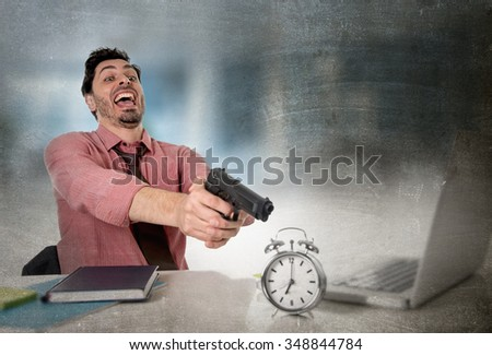 young attractive businessman in stress at office computer desk pointing hand gun to alarm clock in out of time and business project deadline expiring concept in angry frustrated face expression - stock photo