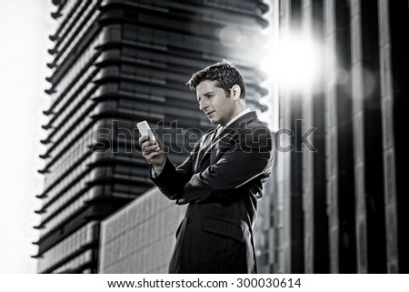 young attractive businessman in suit and necktie looking text message at mobile phone smiling happy standing outdoors in exterior in business district with lens flare - stock photo