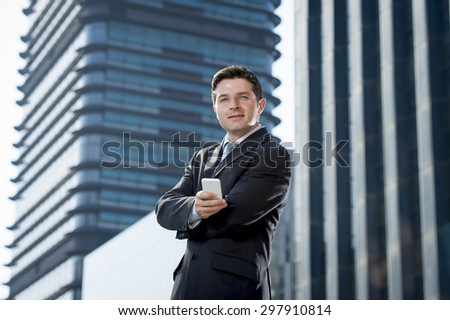 young attractive businessman in suit and necktie talking on mobile smart phone smiling happy and confident standing outdoors in exterior office buildings on business district in success concept