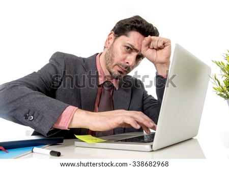 young attractive businessman in suit and tie working in stress at office computer laptop looking desperate and frustrated in work and business problem concept