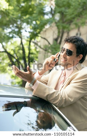 Young attractive businessman leaning on the top of a car in a classic street, smiling while having a phone conversation. - stock photo