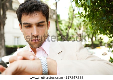 Young attractive businessman looking at the time in his watch while standing in a classic city street, outdoors. - stock photo
