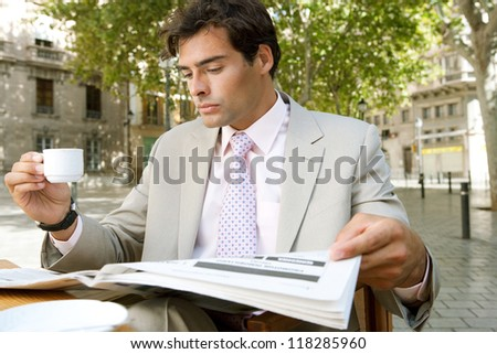Young attractive businessman reading the newspaper while sitting at a coffee shop terrace table, outdoors, in a classic city square with trees. - stock photo