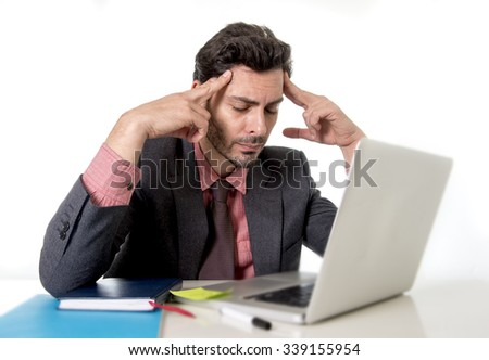 young attractive businessman sitting at office desk working on computer laptop suffering headache fingers on his tempo looking worried in work stress and business problems concept