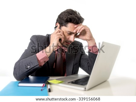 young attractive businessman sitting at office desk working on computer laptop talking on mobile phone overworked looking worried in work stress and  business concept
