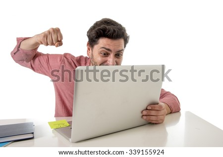 young attractive businessman sitting at office desk working stressed on computer laptop overworked throwing punch in work stress and frustration  concept - stock photo