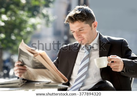 young attractive businessman sitting outdoors for breakfast pause morning reading news in newspaper having a coffee in information media and business people concept - stock photo