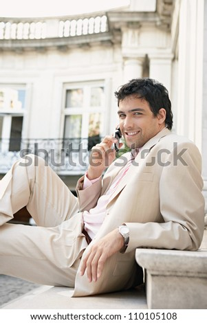 Young attractive businessman smiling and using a cell phone while sitting down on stone steps in a classic building, outdoors. - stock photo