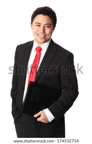 Young attractive businessman standing wearing a suit and red tie. Holding a document folder. White background.