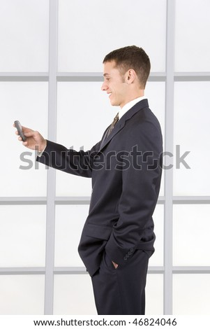 Young attractive businessman texting on a cell phone.
