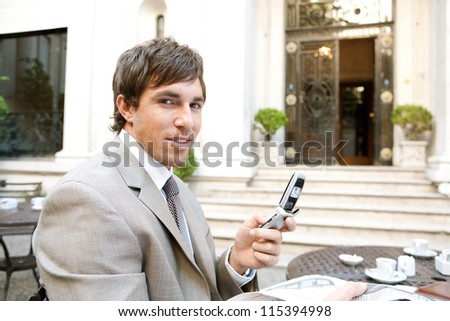Young attractive businessman using a cell phone while sitting in a hotel coffee shop drinking a cup of coffee and reading the newspaper. - stock photo