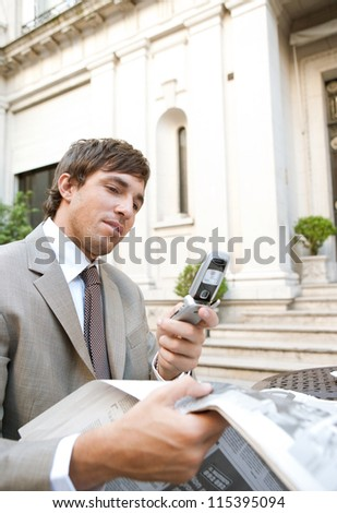 Young attractive businessman using a cell phone while sitting in a hotel coffee shop reading the newspaper. - stock photo