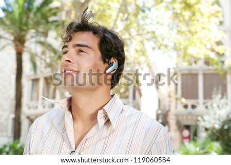 Young attractive businessman using a hands free device to have a conversation on his cell phone while standing in front of classic office buildings in the city. - stock photo