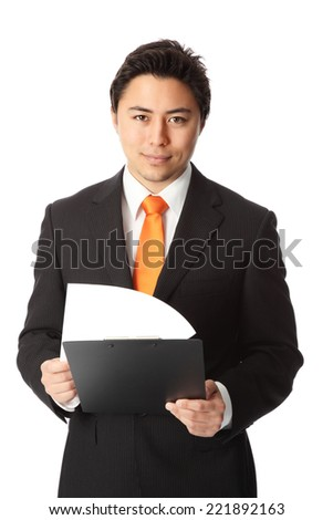 Young attractive businessman wearing a black suit and orange tie. Holding a clipboard. White background.
