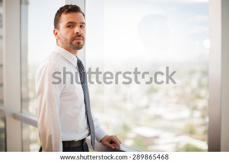 Young attractive businessman wearing a tie and looking confident and serious in an office with a view - stock photo