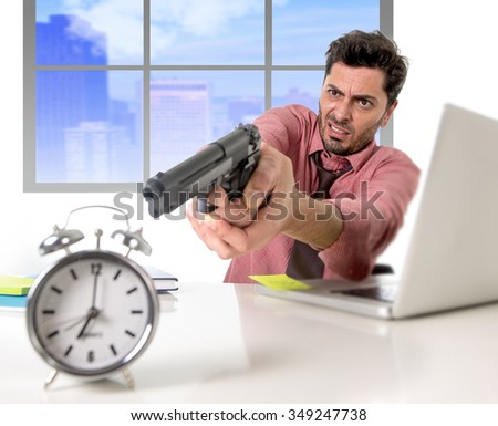 young attractive businessman working at computer desk pointing hand gun to alarm clock in out of time and business project deadline expiring concept angry and frustrated in business district office - stock photo