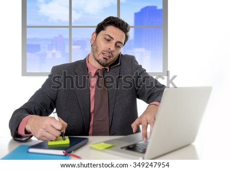 young attractive businessman working on computer laptop taking notes talking on mobile phone overworked multitasking in work stress concept at business district office - stock photo