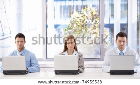Young attractive businesspeople working on laptops individually in bright meeting room.? - stock photo