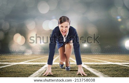 Young attractive businesswoman at stadium standing in start position - stock photo