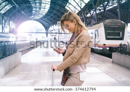 young attractive businesswoman checks the e-mail while waiting for the train. attractive young blonde woman using smart-phone while standing on the railway station platform - stock photo