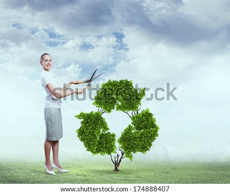 Young attractive businesswoman cutting plant in shape of recycle symbol