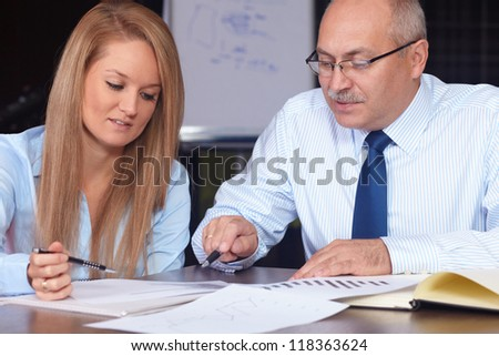 Young attractive businesswoman discuss with senior businessman, background in the office