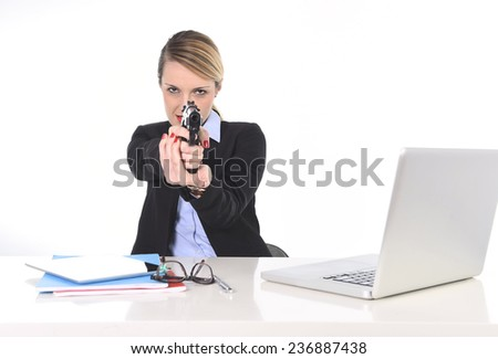 young attractive businesswoman holding and pointing a gun sitting at office desk pointing gun in powerful boss attitude and killer employee concept isolated on white background - stock photo