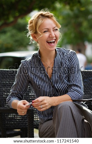 Young attractive businesswoman laughing out loud - stock photo