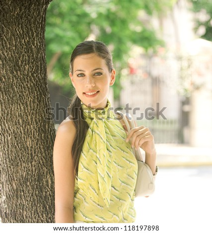 Young attractive businesswoman leaning on a tree trunk in the city, smiling at the camera. - stock photo