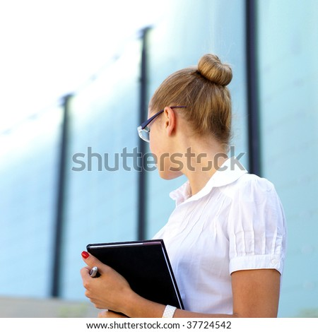 Young attractive businesswoman looking along the business center