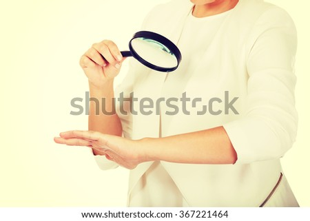 Young attractive businesswoman looking into a magnifying glass - stock photo