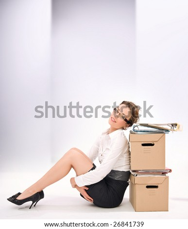 Young attractive businesswoman next to pile of documents, lots of copy space