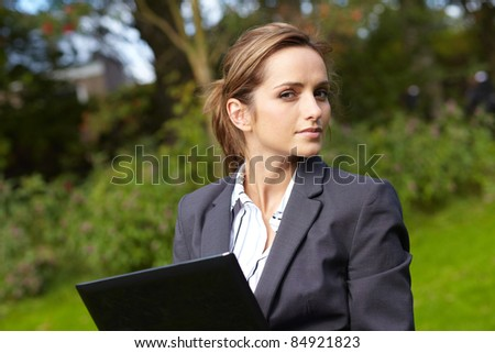 Young attractive businesswoman sits in park and work on her notebook