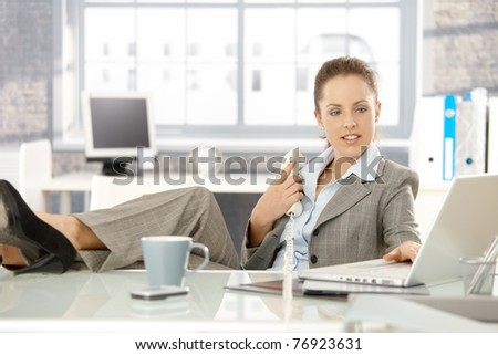Young attractive businesswoman sitting at desk in bright office, holding away phone while checking information on laptop, resting legs on top of desk.? - stock photo