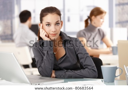 Young attractive businesswoman sitting at desk in office, colleagues working in the background. - stock photo