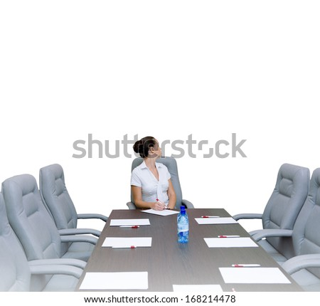 Young attractive businesswoman sitting at head of negotiating table