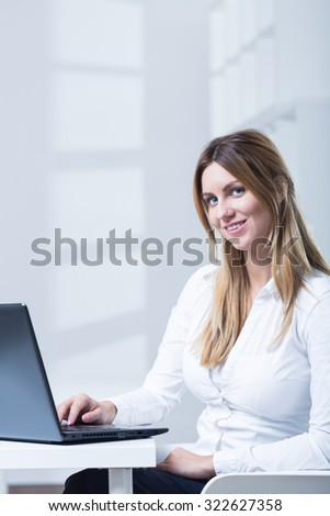 Young attractive businesswoman sitting at the table