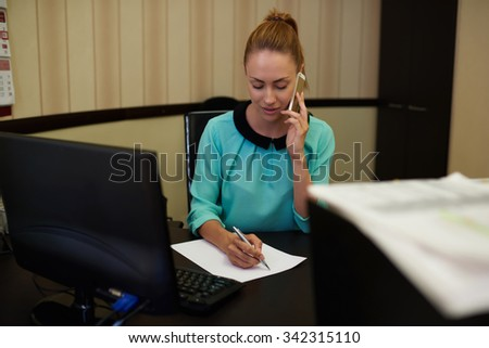 Young attractive businesswoman sitting at workplace and signing papers in comfy office, young female entrepreneur converting on mobile phone next to table pc computer focuses on professional process  - stock photo