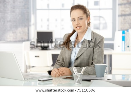 Young attractive businesswoman sitting by desk in office, having laptop.?