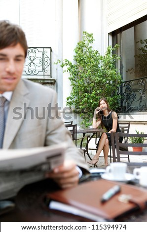Young attractive businesswoman sitting in a luxurious coffee shop terrace using a cell phone and smiling. - stock photo